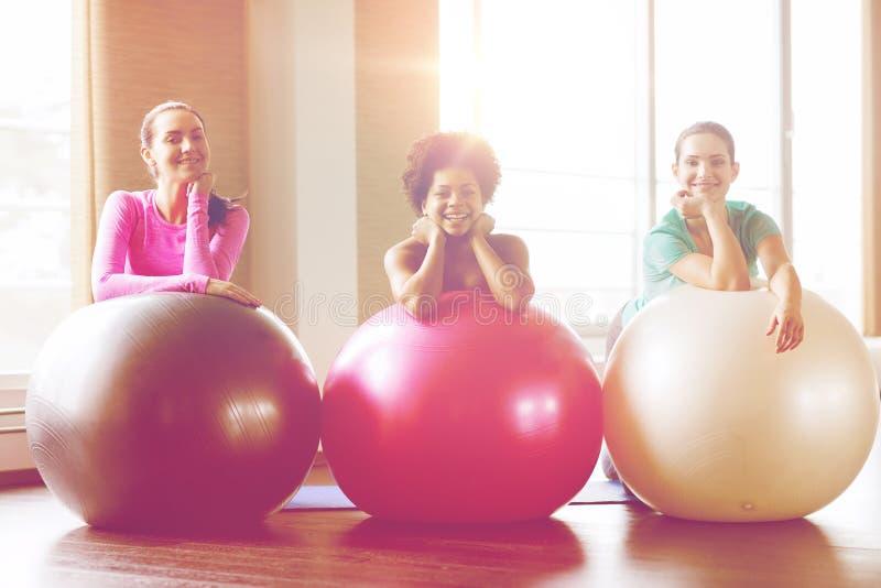 Groep glimlachende vrouwen met oefeningsballen in gymnastiek royalty-vrije stock afbeeldingen