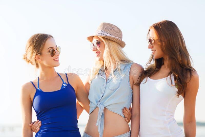 Groep glimlachende vrouwen in zonnebril op strand royalty-vrije stock afbeeldingen