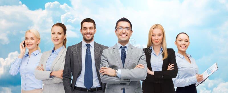Groep glimlachende zakenlieden over blauwe hemel stock afbeeldingen