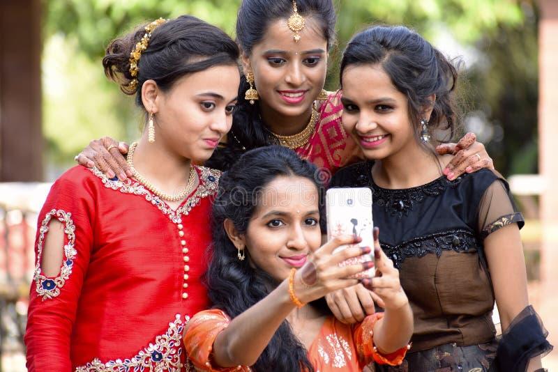 Groep goed geklede meisjes die selfies op telefoon, Pune, Maharashtra nemen stock foto's
