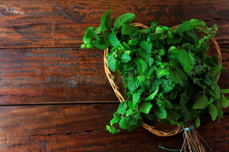 Groep groene organische verse munt in mand over rustiek houten bureau Aromatische pepermunt met geneeskrachtig en culinair gebrui stock foto's