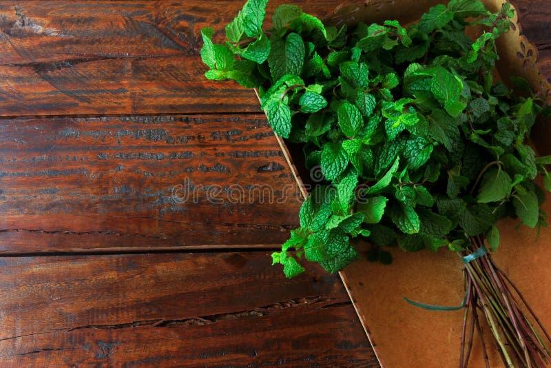 Groep groene organische verse munt in mand over rustiek houten bureau Aromatische pepermunt met geneeskrachtig en culinair gebrui stock afbeelding