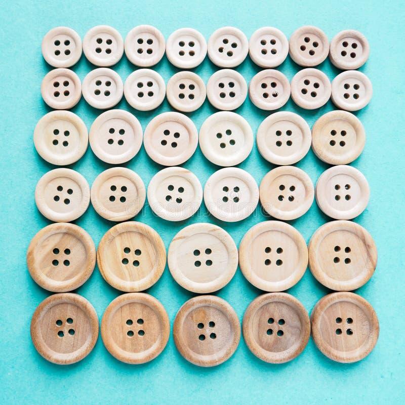 Groep grote en kleine beige houten knopen in rij op blauwe achtergrond stock fotografie