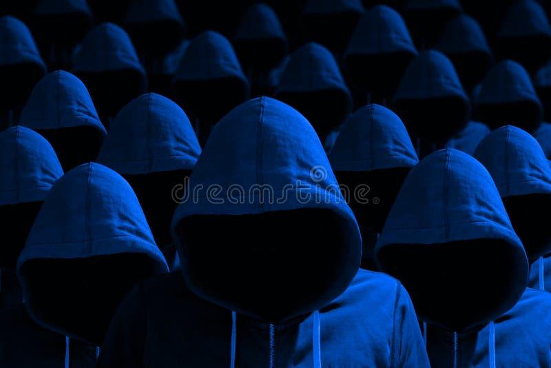 Groep hakkers met een kap in blauw cybersecurityconcept royalty-vrije stock foto's