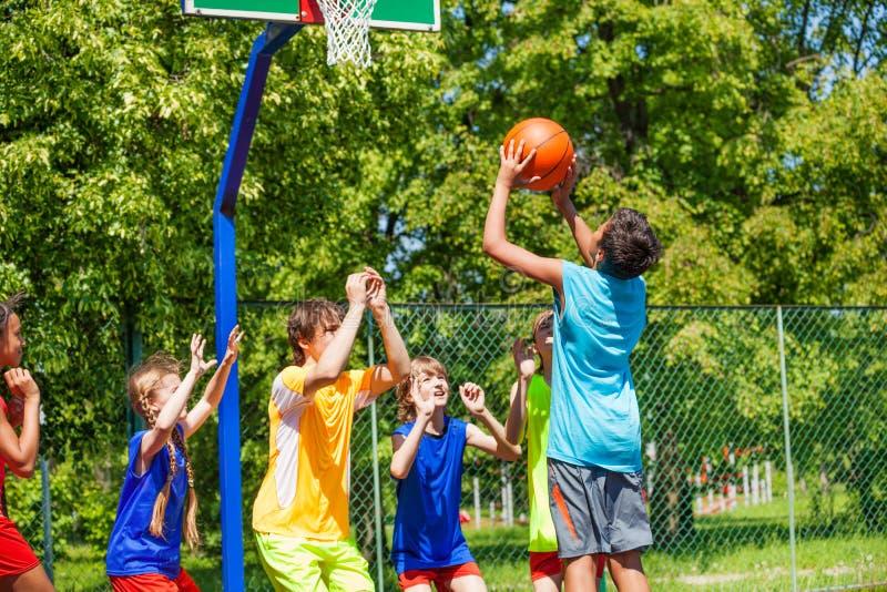 Groep het basketbal van het tienersspel op speelplaats stock afbeelding