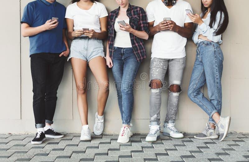 Groep het diverse tieners openlucht gebruiken cellphones royalty-vrije stock foto's