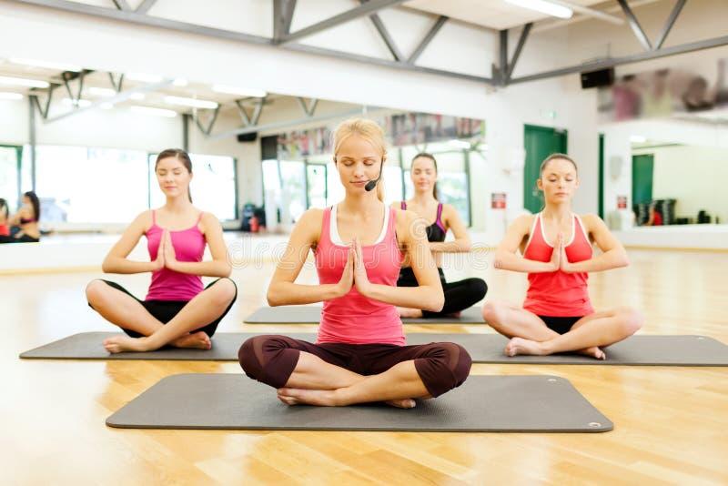 Groep het glimlachen feamle het mediteren in de gymnastiek royalty-vrije stock foto's