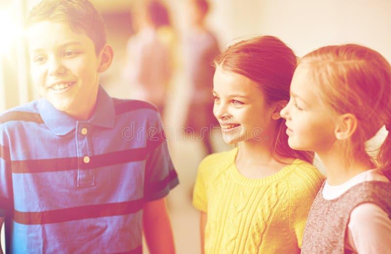 Groep het glimlachen van schooljonge geitjes die in gang spreken royalty-vrije stock foto