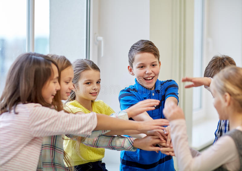 Groep het glimlachen van schooljonge geitjes die handen op bovenkant zetten royalty-vrije stock afbeeldingen