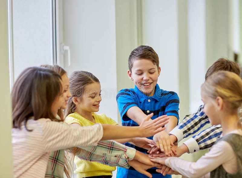 Groep het glimlachen van schooljonge geitjes die handen op bovenkant zetten royalty-vrije stock afbeelding