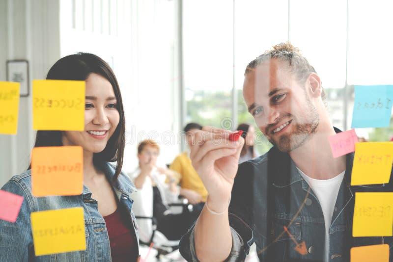 Groep het jonge succesvolle creatieve multi-etnische team glimlachen en uitwisseling van ideeën samen in modern bureau Man en vro stock afbeelding