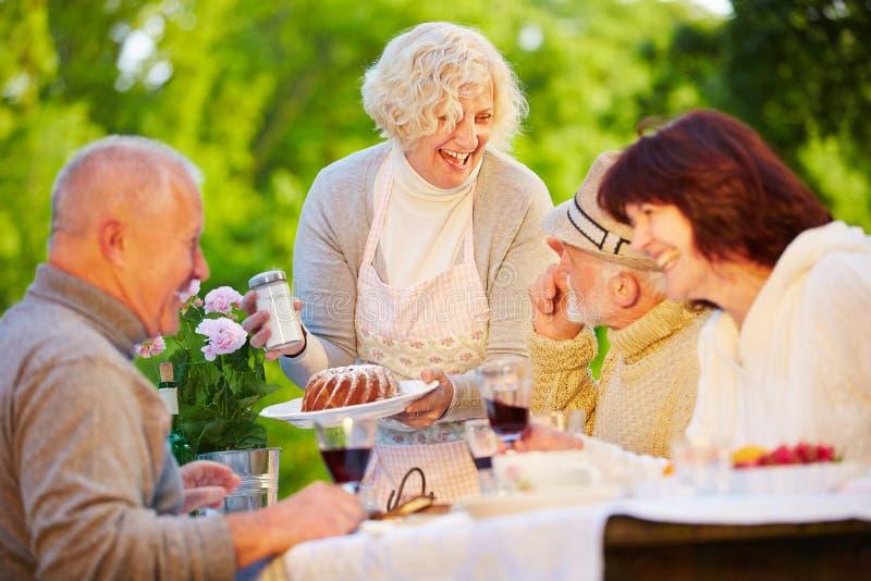 Groep hogere mensen die ringscake eten stock fotografie