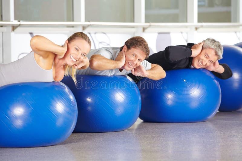 Groep hogere mensen op gymnastiekballen die achter opleiding doen stock afbeeldingen