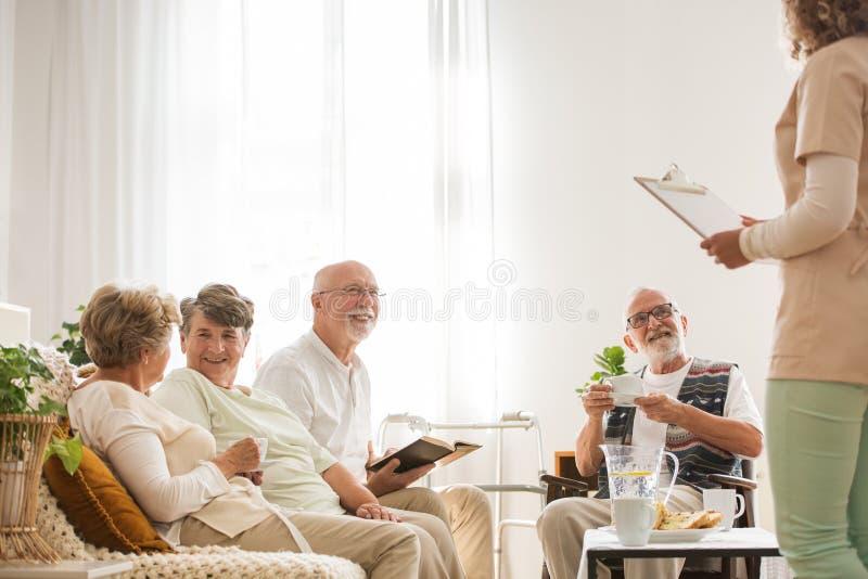 Groep hogere verpleeghuisgepensioneerden die samen bij gemeenschappelijke woonkamer zitten die aan jonge verpleegster luisteren royalty-vrije stock fotografie