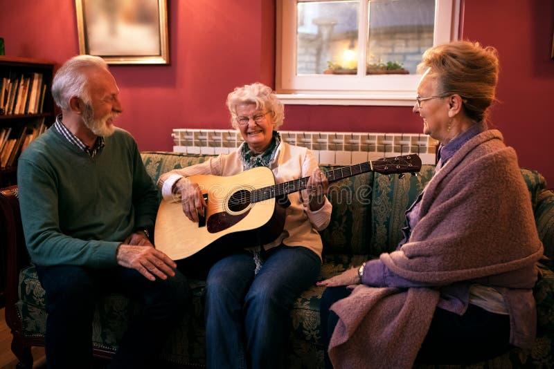 Groep hogere vrienden die gitaar spelen en pret hebben bij verzorging royalty-vrije stock afbeeldingen