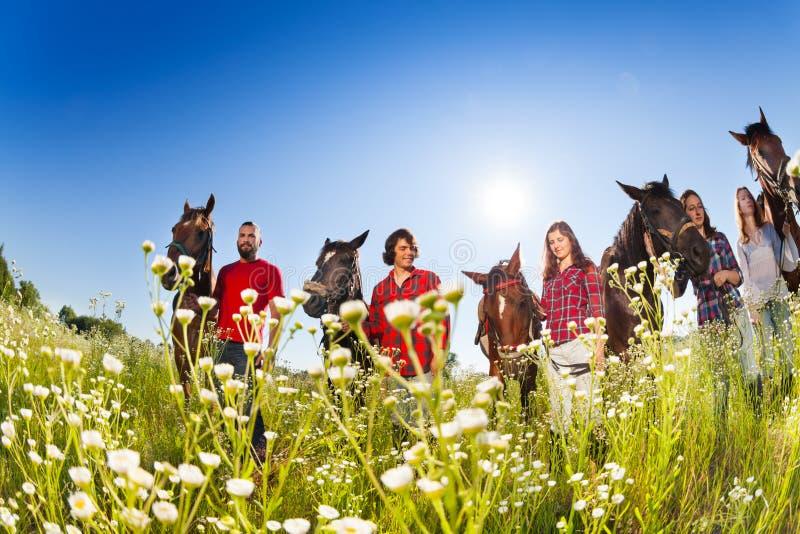 Groep horseback ruiters in bloemrijke weide royalty-vrije stock fotografie