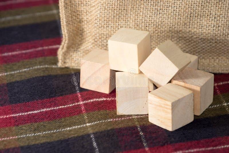 Groep houten kubus op geruit patroontafelkleed met zak bij royalty-vrije stock foto