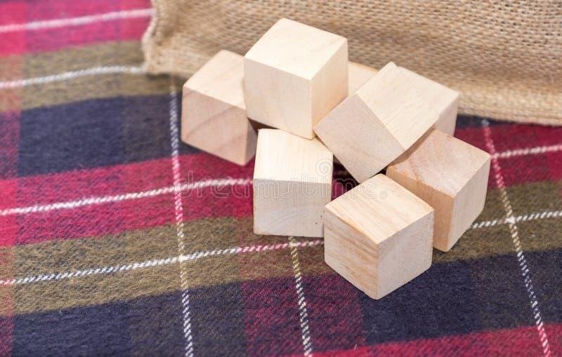 Groep houten kubus op geruit patroontafelkleed met zak bij royalty-vrije stock afbeelding