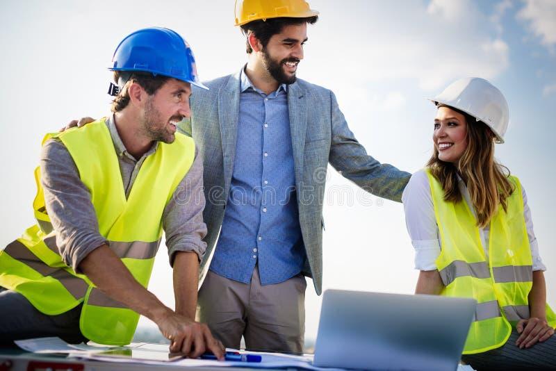 Groep ingenieurs, architecten, partners bij bouwwerf die samenwerken royalty-vrije stock afbeeldingen