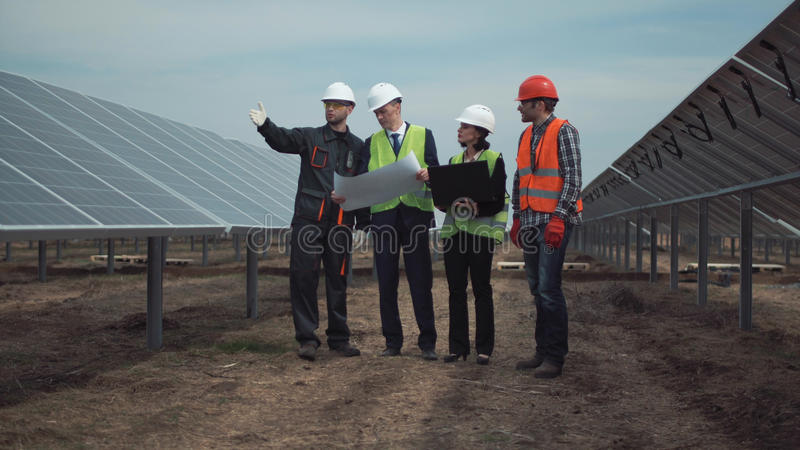 Groep ingenieurs of technici op een zonnelandbouwbedrijf stock foto