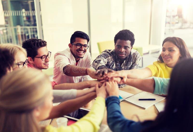Groep internationale studenten met handen op bovenkant stock foto