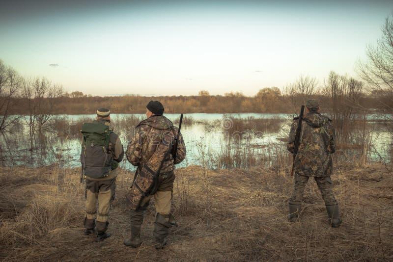 Groep jagers die op landelijk gebied bij rivier tijdens jachtseizoen jagen stock afbeeldingen