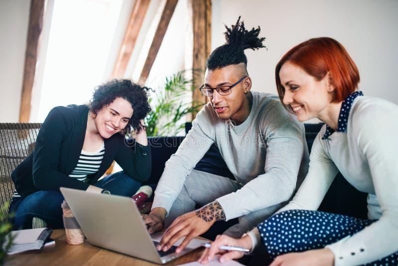 Groep jong zakenlui die laptop in bureau, startconcept met behulp van royalty-vrije stock foto