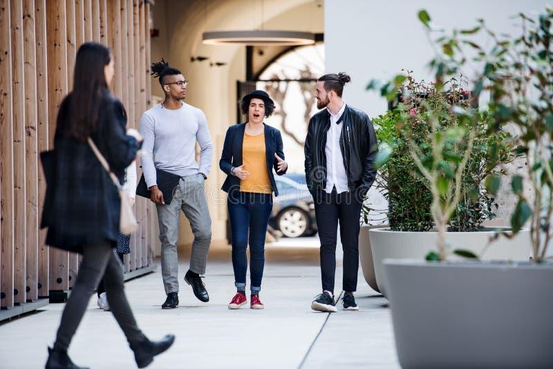 Groep jong zakenlui die in openlucht in binnenplaats, het spreken lopen royalty-vrije stock afbeelding