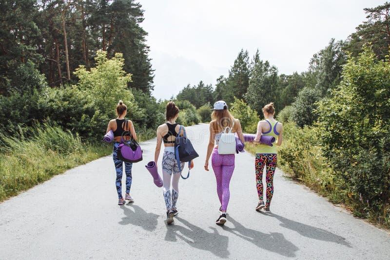 Groep jonge aantrekkelijke vrouwenvrienden met sportuitrusting die voor een training in het Park gaan royalty-vrije stock foto
