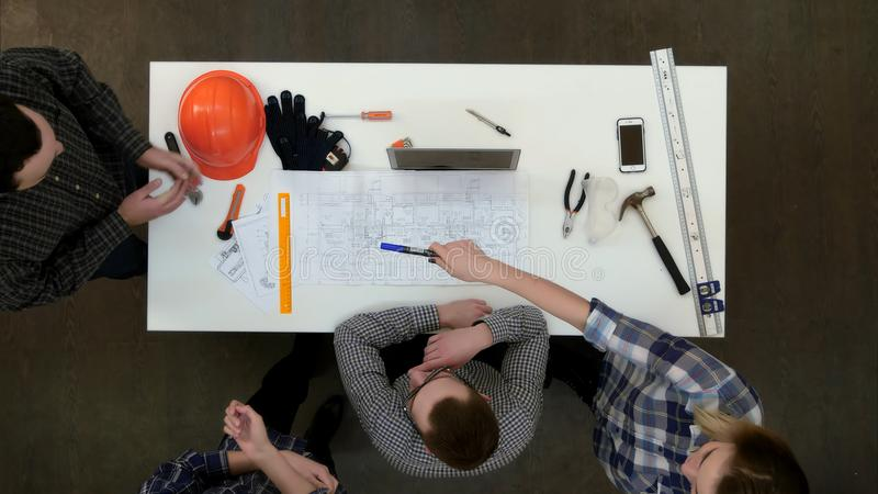 Groep jonge architecten die aan tekeningen werken en metingen met heerser en verdeler maken royalty-vrije stock foto