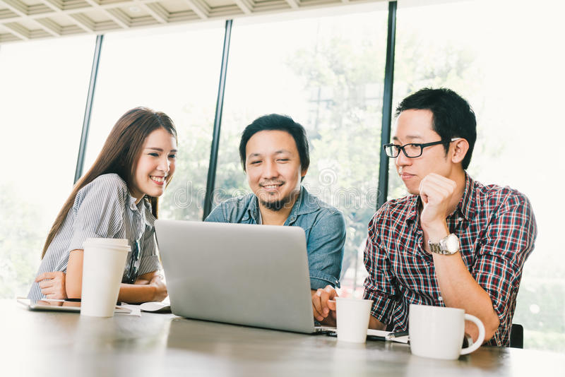 Groep jonge Aziatische bedrijfscollega's of studenten die laptop in team toevallige bespreking met behulp van royalty-vrije stock afbeeldingen