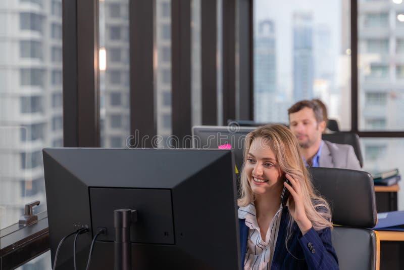Groep jonge bedrijfs en mensen die terwijl samen het zitten bij het bureau werken communiceren stock foto's