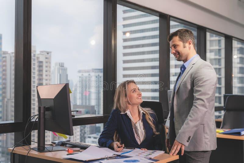 Groep jonge bedrijfs en mensen die terwijl samen het zitten bij het bureau werken communiceren royalty-vrije stock afbeelding