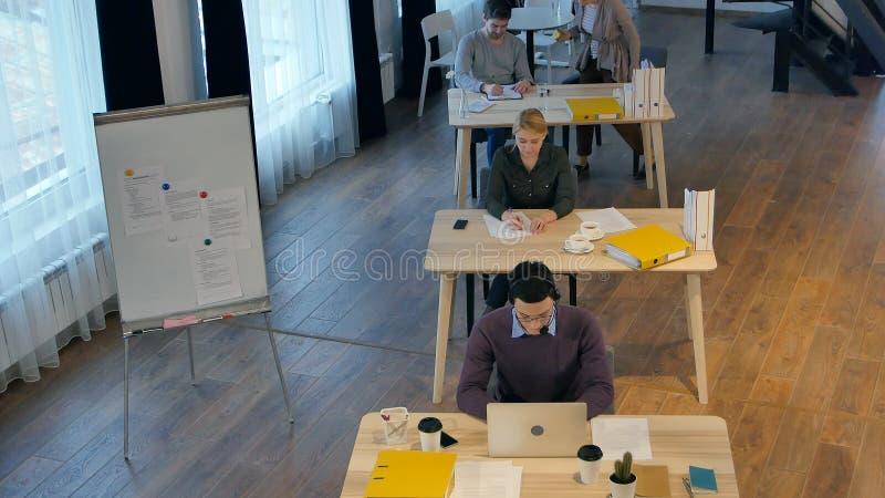 Groep jonge bedrijfsmensen die en in creatief bureau samenwerken communiceren stock afbeeldingen