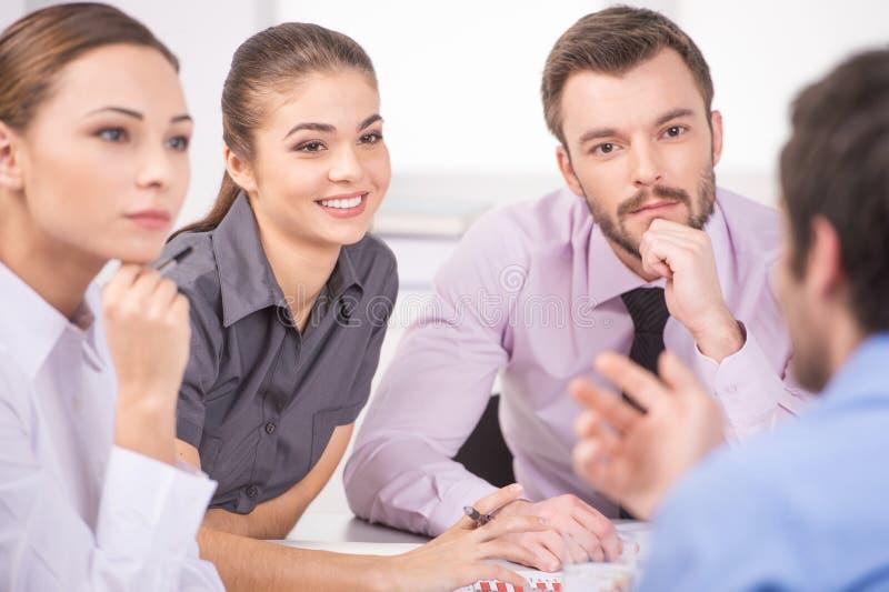 Groep jonge bedrijfsmensen die op commerciële vergadering spreken stock fotografie