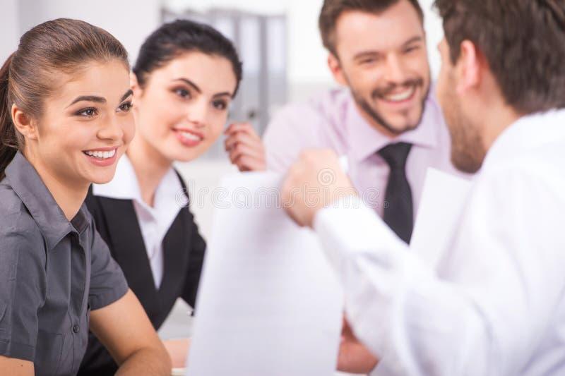 Groep jonge bedrijfsmensen die op commerciële vergadering spreken stock afbeelding
