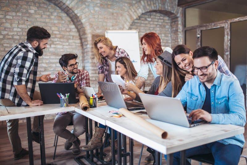 Groep jonge bedrijfsmensen die in slimme vrijetijdskleding samenwerken royalty-vrije stock afbeelding