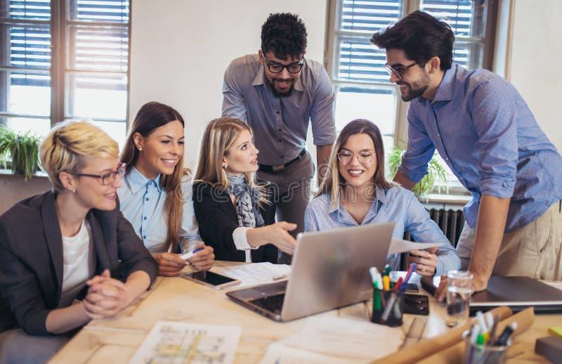 Groep jonge bedrijfsmensen die in slimme vrijetijdskleding samenwerken stock afbeeldingen