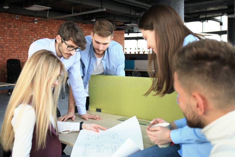 Groep jonge bedrijfsmensen en ontwerpers in slimme vrijetijdskleding Zij die aan nieuw project werken stock afbeeldingen