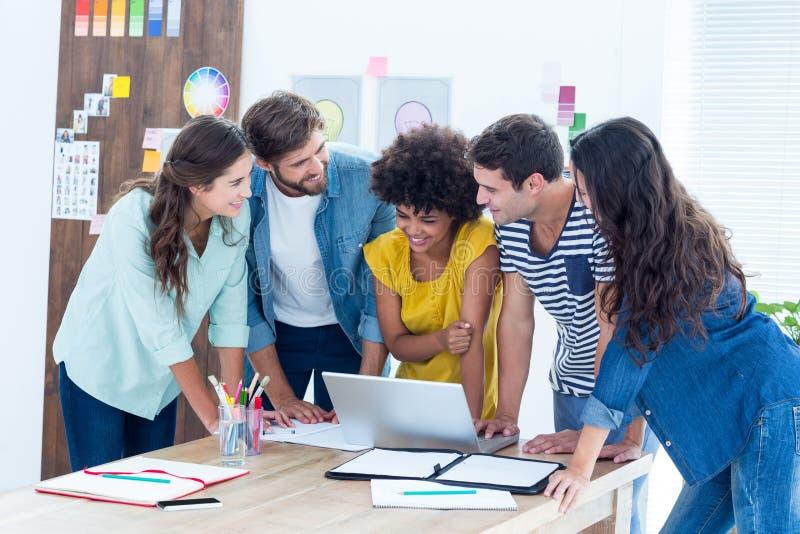 Groep jonge collega's die laptop met behulp van royalty-vrije stock afbeelding