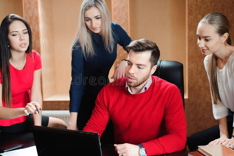Groep jonge collega's die laptop met behulp van op kantoor royalty-vrije stock afbeeldingen
