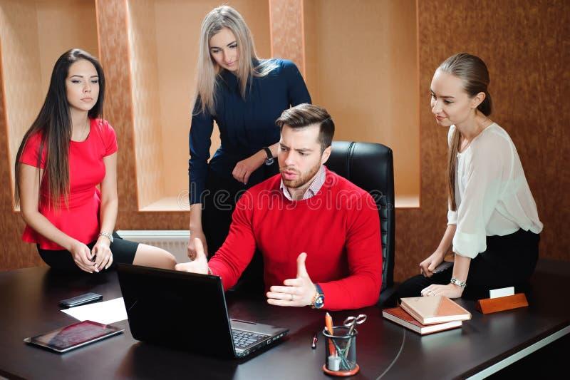 Groep jonge collega's die laptop met behulp van op kantoor stock afbeelding
