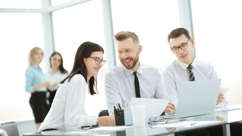 Groep jonge collega's die laptop met behulp van op kantoor stock foto