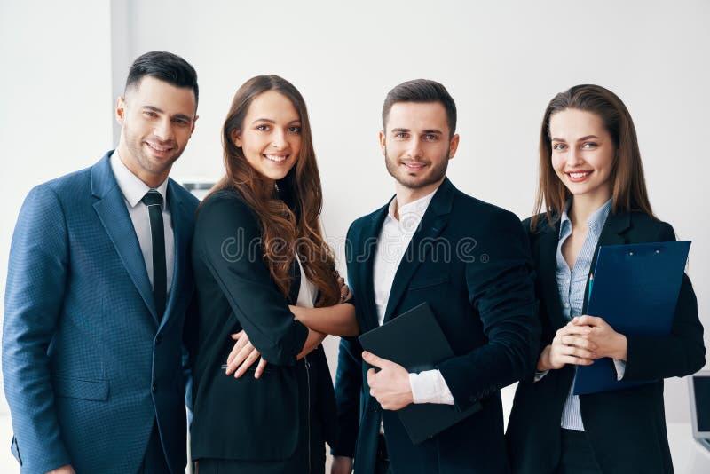 Groep jonge en glimlachende bedrijfsmensen in modern bureau stock afbeelding