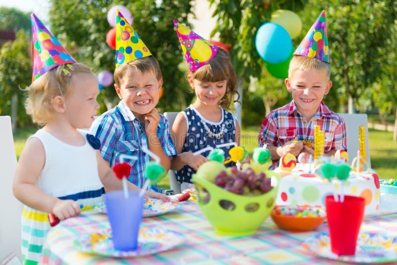 Groep jonge geitjes die pret hebben bij verjaardagspartij stock afbeelding