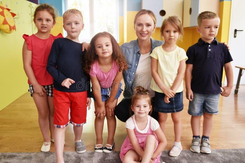 Groep jonge geitjes en leraar in de kleuterschool royalty-vrije stock afbeelding