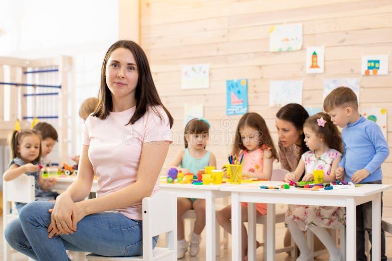 Groep jonge geitjes en opvoeder die het handcrafting samen in klaslokaal in kleuterschool doen stock foto's