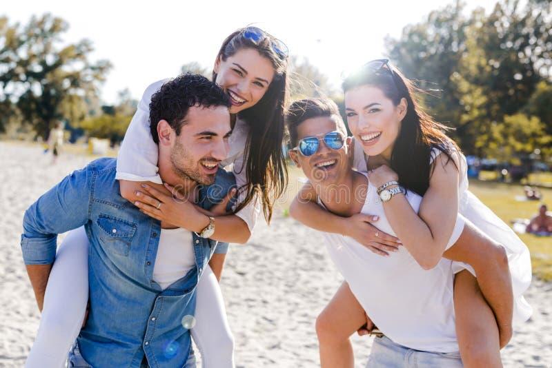 Groep jonge gelukkige mensen die vrouwen op een zandig strand vervoeren royalty-vrije stock afbeeldingen