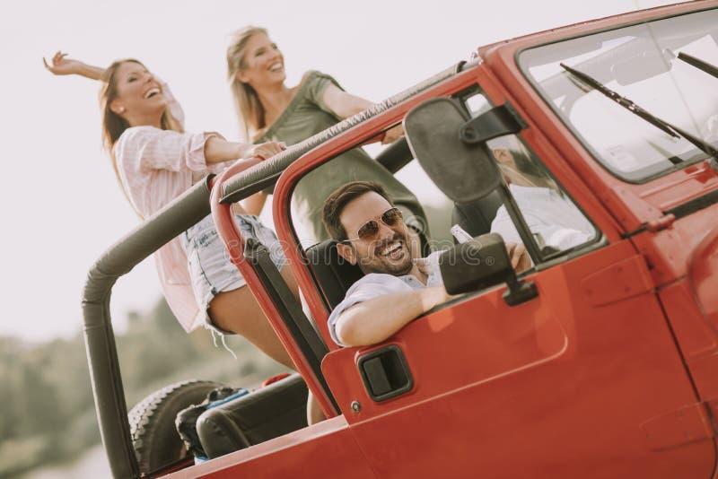 Groep jonge gelukkige mensen die weg van reis in rode convertibel genieten stock foto's