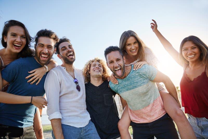 Groep jonge gelukkige mensen die zich buiten verenigen stock afbeelding